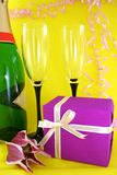 Gift. Surprise gift, champagne and wine glasses on a yellow background Stock Photography
