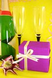Gift. Surprise gift, champagne and wine glasses on a yellow background Stock Photos