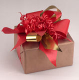 A gift. A small brown parcel decorsted with ties in red and gold Royalty Free Stock Photos