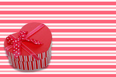 Gift. Color background and a heart-shaped gift pack Royalty Free Stock Photo