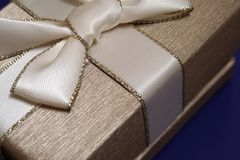 The Gift. A gift wrapped in gold paper with an elegant ribbon Royalty Free Stock Photography