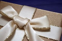 Gift. A gift wrapped in gold paper with an elegant ribbon Royalty Free Stock Image
