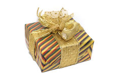 Gift. A gift, colourfully wrapped with a golden ribbon. shallow DOF with focus on parts of the ribbon royalty free stock photos