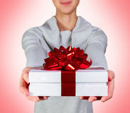 Gift. Smiling woman holding gift box with red ribbon against pink background Royalty Free Stock Photos