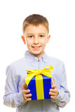 Gift. Boy holding a gift in his hands smiling Royalty Free Stock Photography