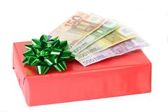 Gift. Red present with green ribbon and Euro bills Royalty Free Stock Photography