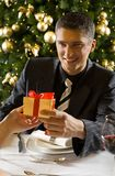 Gift. Young man giving small present during dinner party. He's smiling Stock Photo