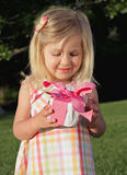 Gift. Pretty little girl in sundress holding a pink birthday present outdoors in summer Royalty Free Stock Photography