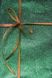 Gift. A gift wrapped in green textured paper and adorned with a yellow ribbon Stock Image