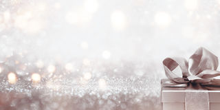 Gift on abstract silver glitter bokeh background. For a festive concept royalty free stock image
