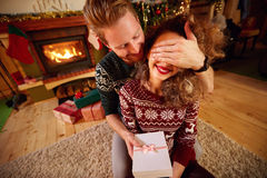 Gift as Christmas surprise. Man giving gift to girl as Christmas surprise Royalty Free Stock Photo