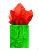 Gift bag. Green Christmas gift bag with red tissue paper isolated on a white background Royalty Free Stock Photography