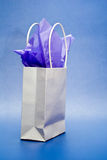Gift Bag. White gift bag with purple tissue paper against a blue background Royalty Free Stock Photography