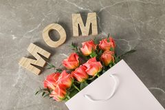 Gift bag with bouquet of orange roses and inscription Mom on brown background. Top view stock photos