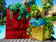 Gift bag, box and ribbon by the swimming pool Royalty Free Stock Image
