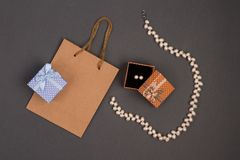 gift bag, gift boxes in polka dots with pearl jewelry on grey ba royalty free stock image