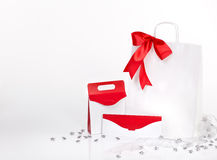 Gift bag and envelope with red ribbon on white Stock Images