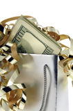 Gift Bag With Money. Silver gift bag and money with gold ribbons against a white background Royalty Free Stock Photo