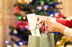 Gift bags and envelopes in a female hand with Christmas tree Stock Photography