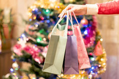 Gift bags in a female hand with Christmas tree Royalty Free Stock Images