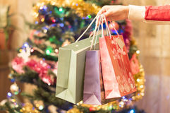 Gift bags in a female hand with Christmas tree Stock Images