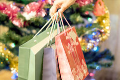 Gift bags in a female hand with Christmas tree Royalty Free Stock Photo