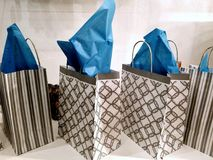 Gift Bags Swag for giveaway at an event. White geometric swag bags with aqua blue tissue paper popping out of the top. Square bag with geometric design royalty free stock photo
