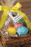 Gift basket for Easter. Colorful  eggs stacked hay in cellophane gift basket for Easter Royalty Free Stock Image