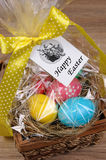 Gift basket for Easter. Colorful  eggs stacked hay in cellophane gift basket for Easter Royalty Free Stock Photo