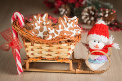 Gift basket-sleigh with cookies, candy and a toy snowman dressed in clothes Stock Image