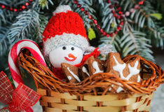 Gift basket-sleigh with cookies, candy and a toy snowman dressed in warm clothes Stock Image
