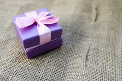 Gift beautiful festive cardboard small gift box with a pink bow on a background of brown linen, self-made, unbleached cloth from v. Violet gift beautiful festive Royalty Free Stock Photography