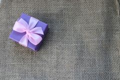 Gift beautiful festive cardboard small gift box with a pink bow on a background of brown linen, self-made, unbleached cloth from v. Violet gift beautiful festive Stock Photography