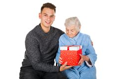 Gift for a beautiful grandmother. Picture of an old lady receiving birthday gifts from her grandson stock photography