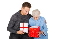 Gift for a beautiful grandmother. Picture of an old lady receiving birthday gifts from her grandson royalty free stock photography