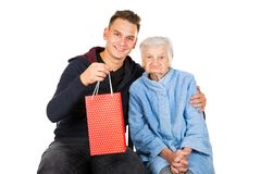 Gift for a beautiful grandmother. Picture of an old lady receiving birthday gifts from her grandson stock images