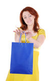 Gift from beautiful hands. Young beautiful woman with blue paper bag in her hands on white background. Focus on woman's hands Stock Images