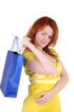 Gift from beautiful hands. Young beautiul woman with blue paper bag on her finger on white background Stock Images