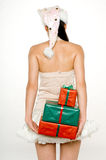 Gift Behind Back. A young attractive woman in santa hat and skirt with gifts behind her back Stock Images