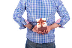 Gift behind back. Young man hiding a gift behind his back, guy wearing blue shirt, isolated on white background Royalty Free Stock Images