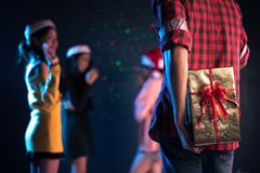 Gift in the behind of man who will surprise woman in dancing pub or bar, Couple and Lovers concept. Gift in the behind of men who will surprise women in dancing stock photography