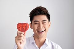 A gift for the beloved. Young beautiful smiling elegant man in a white shirt holding a box with a gift and shows it to the camera. Valentine`s Day royalty free stock photo