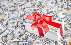 Gift  with big red bow ribbon made of united states dollars curr. Ency bundle on many new one hundred USA money banknotes background. Financial successful Royalty Free Stock Image