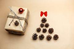 Gift bij ecostijl wordt ingepakt met de nieuwe rode bellen die van de jaarboom en pinecones Stock Fotografie
