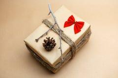 Gift bij ecostijl wordt ingepakt met rode bellen, pinecones en boog die Stock Fotografie
