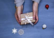 Flat lay of woman hands holding gift wrapped and decorated with bow on blue background with copy space stock photos