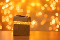 Gift on blurry New Year lights background stock photos