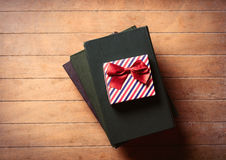 Gift and books. Photo of the gift and books on the brown wooden background Stock Photography