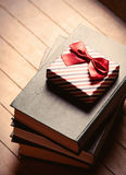 Gift and books. Photo of the gift and books on the brown wooden background Royalty Free Stock Photography