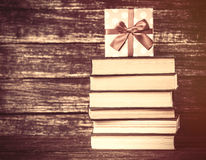Gift and books on wooden table. Royalty Free Stock Photo